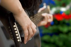 Guitar Christmas. Hands playing a guitar, with a Christmas tree in the background.  Hand and strings in foreground in focus.  Narrow depth of field Royalty Free Stock Photos