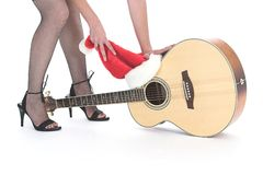 Guitar at Christmas time. Placing christmas hat over guitar Stock Photo