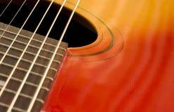 Guitar closeup. Red and yellow guitar closeup with strings Stock Photography