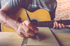 Guitar composion. Young man composing the song with guitar on table Stock Photography