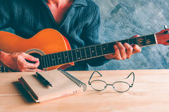 Guitar composion. Young man composing the song with guitar on table Royalty Free Stock Image