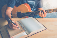 Guitar composion. Young man composing the song with guitar on table Royalty Free Stock Images