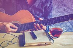 Guitar composion. Young man composing the song with guitar on table with tea cup Stock Photo