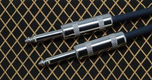 Guitar cord plugs. Against tweed speaker cloth Royalty Free Stock Photo