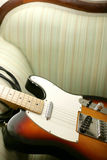 Guitar on couch Stock Photos