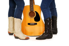 Guitar and Cowboy Boots. Ladies legs in Cowboy Boots and an acoustic country guitar isolated royalty free stock image