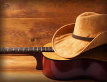 Guitar and cowboy hat on wood background. For text or design royalty free stock images