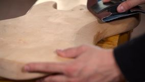 Guitar craft. Hands of guitar maker smooth wooden an electric guitar body. Shot with Sony A7s and Canon lens macro 100mm stock video