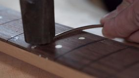 Guitar craft. Hands of the producer of a guitar fix frets in a guitar neck. Shot with Sony A7s and Canon lens macro 100mm stock video footage