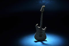 Guitar on a dark stage with spotlight Stock Photos