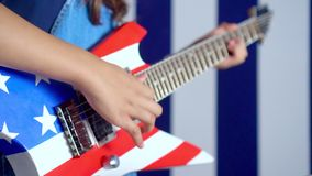On a guitar the drawing of the American flag. The girl has fun with a guitar in hands. Young girl with guitar having fun
