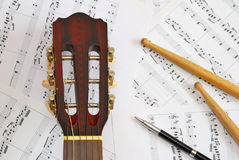 Guitar, drum sticks with pen on music score Stock Photo