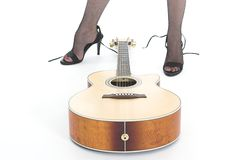 Guitar and Feet. Legs in high heels behind guitar Royalty Free Stock Image