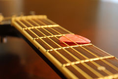 Guitar fingerboard. Acoustic guitar fingerboard and pink pick Stock Photos