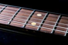 Guitar fingerboard. Detail of vintage electric guitar fingerboard on dark background Stock Photo