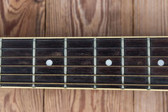 Guitar fingerboard. On wooden background royalty free stock photo