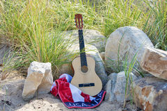 Guitar with flag towel on beach sand Stock Photos