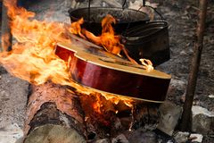 Guitar in flame and two old sooty cauldrons. On campfire at forest royalty free stock photo