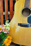 Guitar and Flowers Background Close-up. Close-up of a wooden guitar and flowers with wood slat background Stock Photos