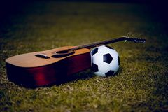 Guitar and football are placed in green lawns. Music and sports stock photos
