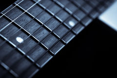 Guitar fret board. Detail of the fret board of an acoustic guitar, on a dark background Stock Images