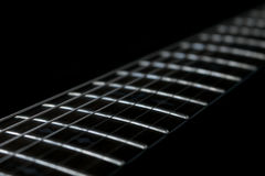 Guitar fretboard. Close up in a black background royalty free stock image