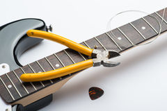 Guitar frets with string, mediator and yellow nippers. On white Royalty Free Stock Photo
