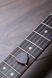 Guitar frets with strings and mediator on dark brown surface Stock Photography