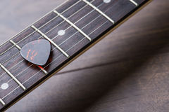 Guitar frets with strings and mediator on dark brown table Stock Photo