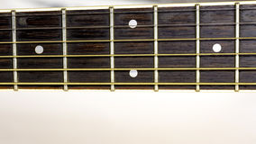 Guitar frets with strings run down the neck Royalty Free Stock Photos