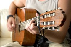 Guitar fretting hand in motion. Man playing guitar.  Focus and depth of field are set for the fretting hand.  Motion blur Royalty Free Stock Photos