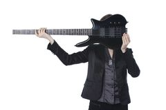 Guitar-girl. Girl in a classic black dress holding horizontally at the level of heads of the electric bass guitar. It seems that the girl's head instead of Stock Photography