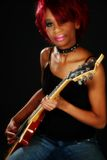 Guitar Girl. Beautiful young African American woman sitting on amp holding electric guitar over black royalty free stock photos