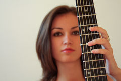 Guitar Girl. Portrait of a young beautiful girl next to an acoustic guitar royalty free stock photo