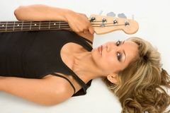 Guitar girl On the floor. Beautiful Girl laying on the floor with bass guitar Stock Image