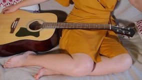 The guitar is on the girl`s legs. Guitar lies on the legs of the girl, close-up stock video footage