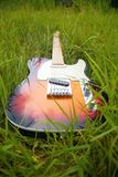 Guitar in grass Royalty Free Stock Photos