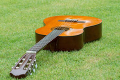 Guitar on the grass. Figure guitar laying on the grass in the daytime Stock Photo