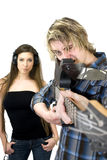 Guitar Gun. A male holds guitar squinting like he's looking down the barrel of a gun. A female stands in the background wearing Headphones with a neutral Royalty Free Stock Photos