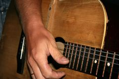 Guitar and hand. Closeup of guitar and muscian's hand Royalty Free Stock Photography