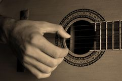 Guitar and Hand. Large Hand playing Guitar in Sepia Tone Stock Photo