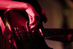 Guitar Hand. And guitar on a live music stage Stock Image