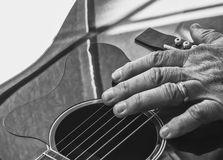 Guitar And Hand Detail. Close-up monochrome view of guitar and man's hand Stock Photo