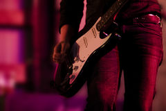 Guitar Hand and Legs. Guitar players hand, legs holding a guitar Stock Photos
