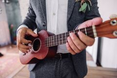 Guitar with hands of the groom, close-up. Ukulele, hands of the groom with wedding ring. Romance, love, family.