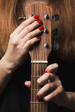 Guitar in the hands of a woman playing musical instrument. Guitar in the hands of a young red-haired woman who grasps the strings and playing a stringed musical Royalty Free Stock Photo