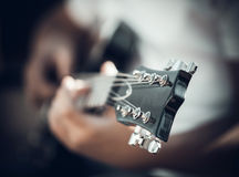 Guitar in the hands of the young man Stock Photos