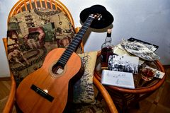Guitar with a hat on the fingerboard lies on a rocking chair near the glass table. With scattered old photographs and with a bottle and a glass of alcohol stock photo