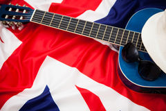 Guitar, hat and glasses on the background of the flag of Britain Stock Images