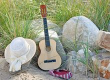 Guitar with hat and shoes on beach Royalty Free Stock Images